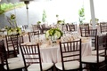 Wedding reception table with a pink tablecloth and green and white flowers