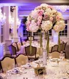 Wedding reception centerpiece of white, green, purple hydrangeas, pink, white roses in trumpet vase
