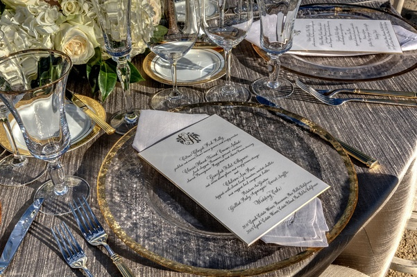 Outdoor wedding place setting with grey tablecloth and gold plate