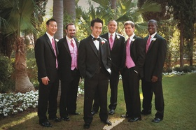 groomsmen wear black suits with pink ties and vests