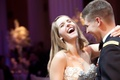 Bride and groom in Dress Blues laugh as they dance