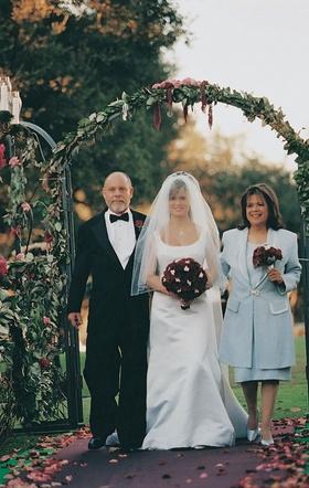 Bride and parents walk through ceremony gate entrance