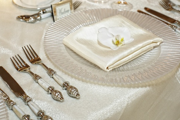 Pearl charger plate with white orchid and pearl silverware