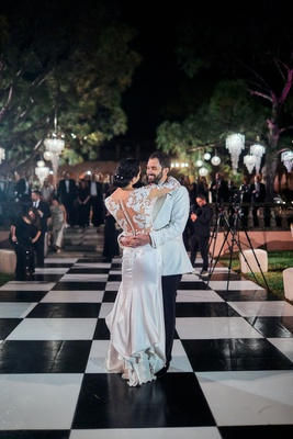 bride and groom first dance on black-and-white checkered dance floor