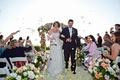 Bride and groom walk up aisle with rose petal toss