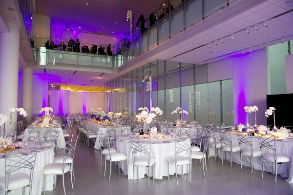 White tables with silver chairs in reception room with purple lighting
