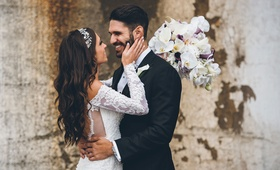 Bride in off shoulder lace wedding dress holds groom's face after first look wedding photos