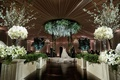 Bride and groom on circle stage chuppah greenery flower chandelier white rose hedge wall topiary