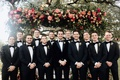 groom with groomsmen in tuxedos bow ties groom with feather bow tie pink greenery chuppah