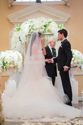 bride in nardos deisgns lace mermaid gown dabs eyes with tissue, hold hands of groom in tuxedo