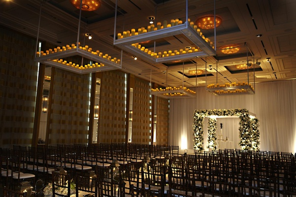 Square platforms with candles hanging from wedding ceiling