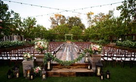 raised platform jewish wedding ceremony greenery small candles lanterns alfresco