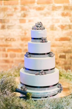 White wedding cake with navy blue ribbons, rhinestone bands, and clusters of blackberries