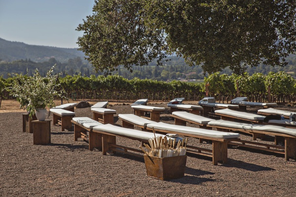 Wedding ceremony in wine country california wood bench with white cushion parasols greenery