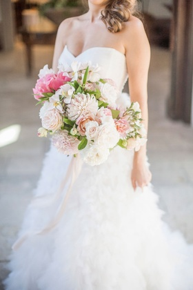 Bride in strapless sweetheart neckline Monique Lhuillier bouquet with pink peony dahlia rose flowers