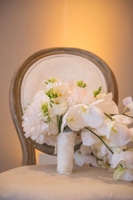 Bride's bouquet of white peonies, orchids, lisianthus bound by lace