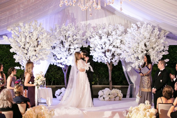 wedding ceremony white cherry blossom trees tented terrance guests clapping female officiant