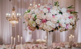 Tall wedding reception arrangement of blush, white hydrangeas, roses