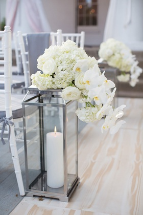 Silver lantern with candle inside decorated with white hydrangea rose and orchid flowers ceremony