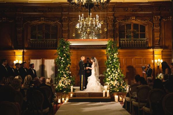 wedding ceremony wood panel ballroom chuppah greenery white flowers candle chandelier aisle runner