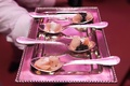 bite sized hors d'oeuvres being served in spoons on a silver tray under pink lighting
