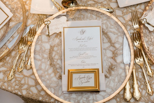 clear charger with gold trim, gold framed place card, gold flatware, textured linens