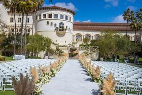 outdoor wedding ceremony monarch beach resort pampas grass lining aisle runner white chairs rotunda