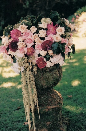 Four foot tall urns filled with flowers at ceremony