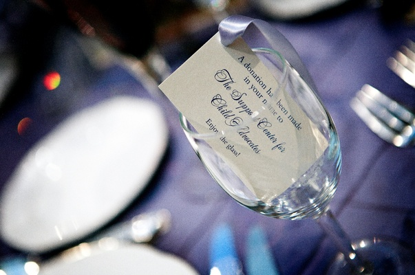 Wedding favor of a card stating that a donation was given to a charity on behalf of the guest