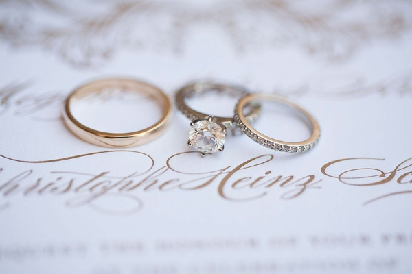 a six-prong engagement ring and a brides diamond studded band a grooms gold band wedding invitation