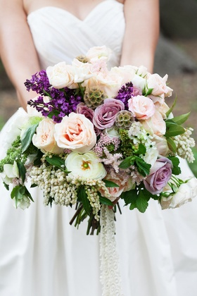 Bride's bouquet for outdoor wedding with pink and purple roses, white and purple flowers, greenery