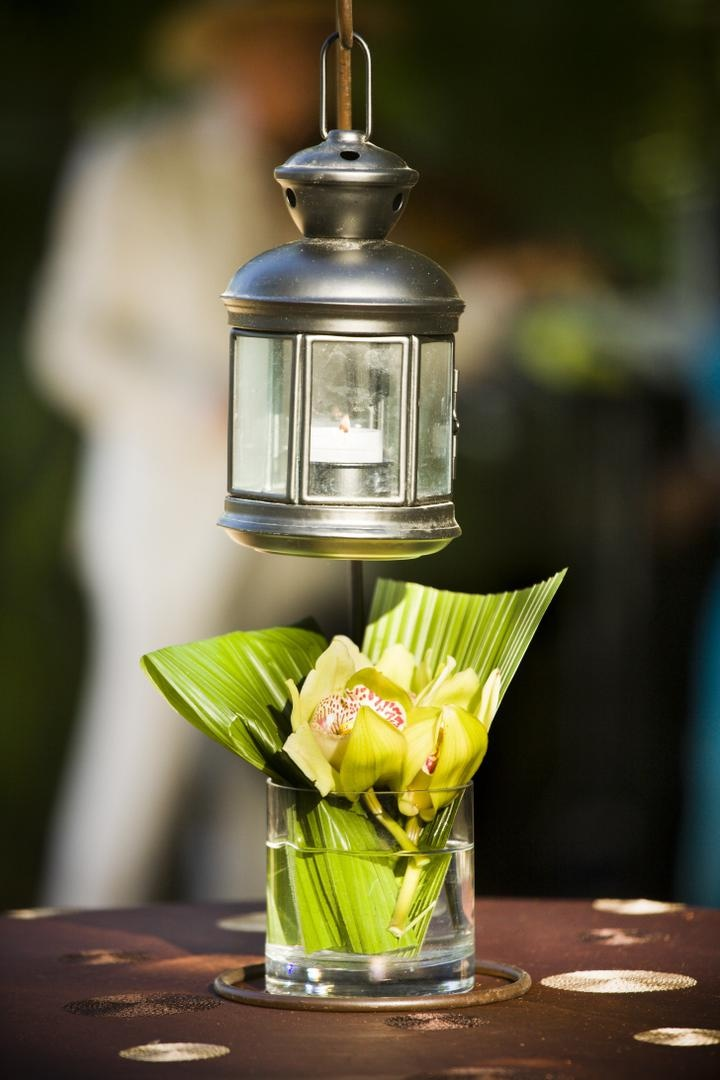 Green orchid and leaf arrangement with silver lantern