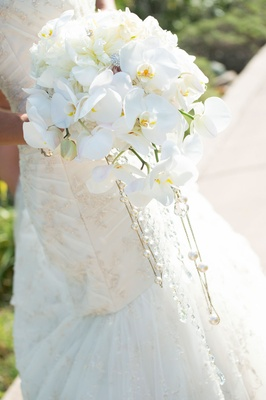 Bride holding cascading bridal bouquet featuring ivory orchid, rose, and jewel arrangement