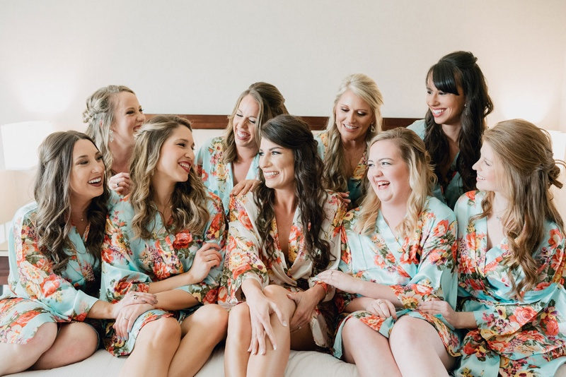 Wedding party bridesmaids on bed in matching silk robes mint and pink flower design print curled hai