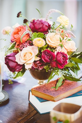 Outdoor bohemian wedding reception table, aged books, pink, red, peach flowers, greenery
