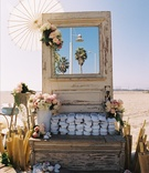 Ceremony parasols and slippers on rustic beach display