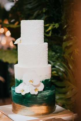 wedding cake with four layers gold and green brush stroke paint design textured top layers orchid