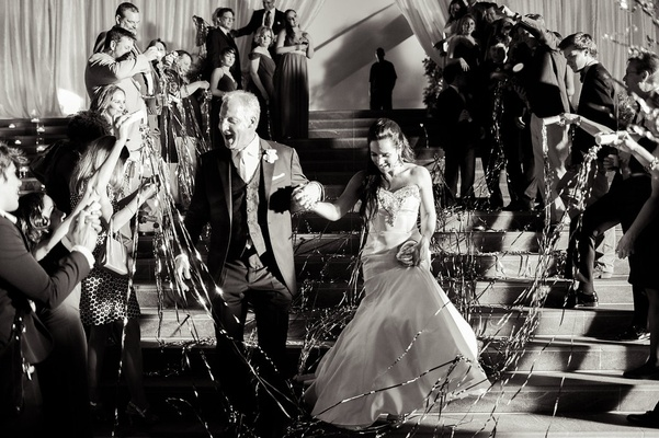 bride and groom exiting reception streamers guests black and white trumpet gown tuxedo smiles