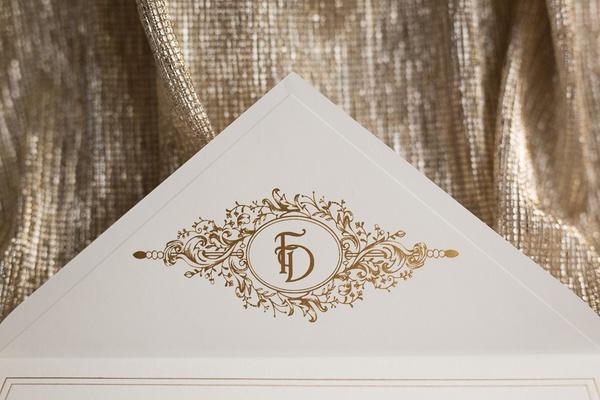 ivory wedding invitation envelope with embellished gold monogram on inner point