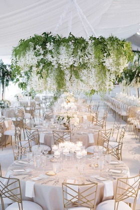 wedding reception white tent greenery chandelier gold chairs candles low centerpiece