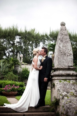 Bride and groom kiss on grounds of The Breakers