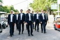 Groom and groomsmen in suits and bow ties sunglasses walking on bahamas streets harbour island