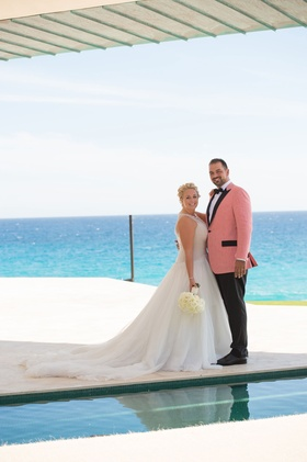 oceanside wedding portrait, bride in mark zunino, groom in salmon tuxedo jacket