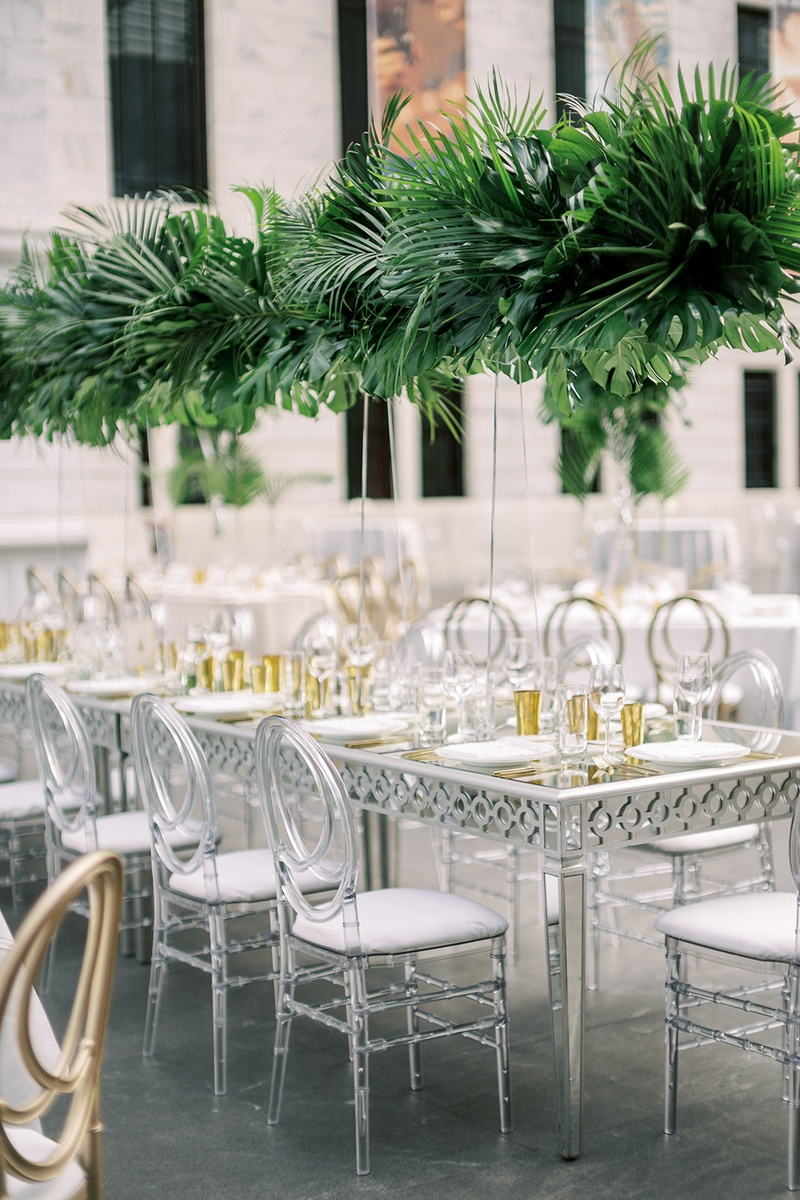 wedding reception long silver and mirror table with oval lucite acrylic chairs tall tropical