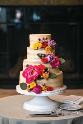 semi-naked, lightly frosted, small four-tiered cake with bright pink, yellow, and lavender flowers