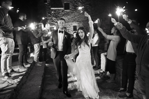 black & white photo of bride & groom making grand exit from their wedding as guests wave sparklers