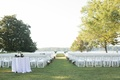 Plantation wedding ceremony overlooking lake with magnolia flowers in hurricane vases white chairs