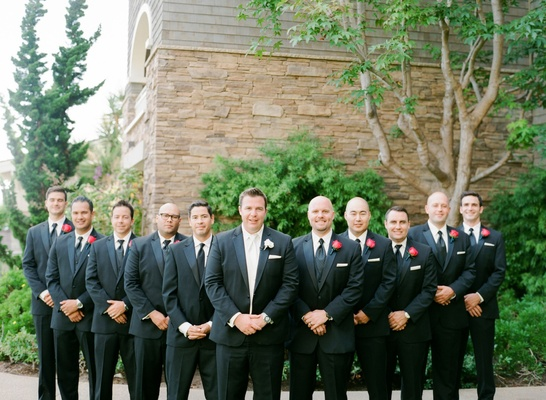 Groom in white tie and tux with groomsmen in black suits