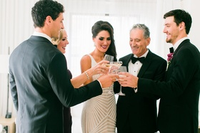 Bride in Naeem Khan wedding dress with father and mother of bride and bridesmen toasting champagne