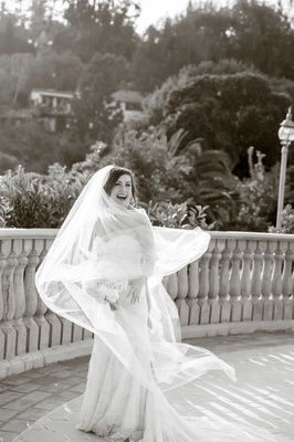 black and white photo of twirling bride smiling bouquet balcony bel-air bay club california